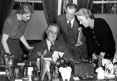 President Roosevelt in his study in with three secretaries: (l. to r.) Marguerite LeHand, Marvin McIntyre, and Grace Tully. November 4, 1938. FDR Library Photo Collection.